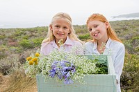 Two girls carrying a box of flowers and smiling