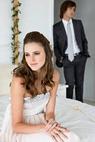 Bride sitting on the bed with groom standing behind her