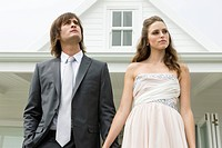 Newlywed couple in front of a house