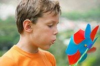 Boy blowing on pinwheel