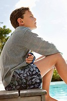 Boy day dreaming near a swimming pool