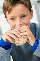 Portrait of a boy eating a bun