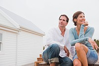 Couple sitting in front of a house