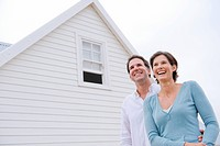 Couple smiling with a house in the background