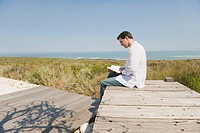 Man sitting on a boardwalk and reading a book