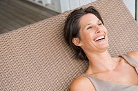 Woman lying on a porch swing and smiling