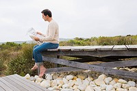 Man sitting on a boardwalk and reading a newspaper