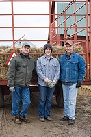 Three farmers by tractor of hay
