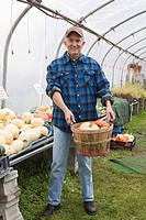 Farmer in greenhouse with pumpkin