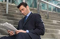A businessman sitting on steps with a newspaper