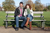 A couple sitting on a park bench