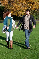 A mid adult couple hold hands in dulwich park