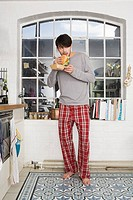 Young man eating burger in kitchen