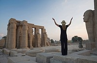 Woman tourist with arms raised at the Ramesseum, Egypt