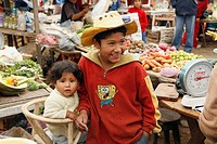 Young boy with baby in marketplace, Lima, Peru