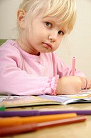 Stock photo of a four year old girl drawing pictures on a piece of paper