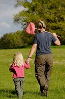 Stock photo of a mother and her 3 year old daughter walking hand in hand across a field as they go on a fishing trip