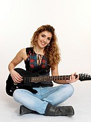 Young woman playing guitar electronica.