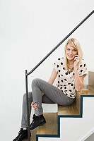 Young woman on cellphone on stairs