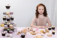 Girl with table of cakes