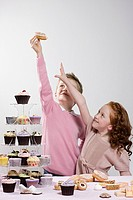 Girl reaching for doughnut that boy is holding