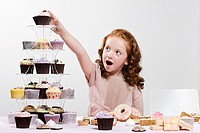 Girl reaching for cake