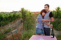 Couple in a field with table and wine