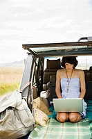 Young woman using laptop in back of suv