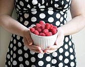 Woman in Polka Dots Holding Bowl of Raspberries