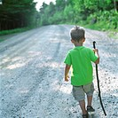 Young Boy with Stick Walking Down Path