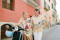 Man and woman with scooter reading map