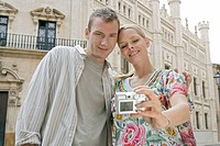 Man and woman with digital camera taking self_portrait