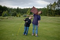 Two boys being playful on a golf course