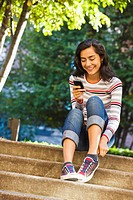 Hispanic woman text messaging with cell phone