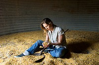 Female farmer sitting in corn silo