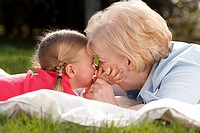 Outdoor portrait of grandmother and granddaughter kissing
