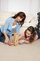 Two girls playing a stacking block game