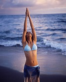Indian girl doing the Salutation to the Sun yoga posture on the beach