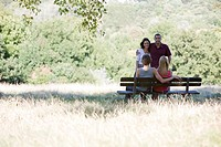 Two young couples talking by a bench in a park