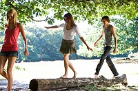 Three young people in a park, two balancing on a log