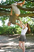 A young man hanging from a tree, girlfriend pulling on his T_shirt