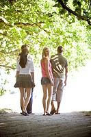 Four friends walking along a path in summertime