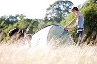 Two young men setting up a tent in a field