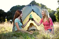 Three young women camping, two drinking beers (thumbnail)