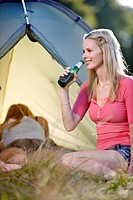 Two young women camping, one drinking a bottle of beer (thumbnail)