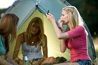 Three young women camping, one applying make-up (thumbnail)