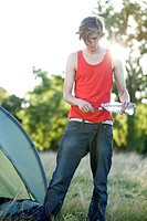 A young man camping, pouring water on his toothbrush