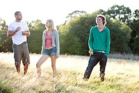 Three young friends standing in a field, one eating