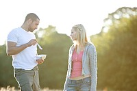 A young couple standing in a field, man eating (thumbnail)