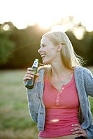 Portrait of a young woman drinking a beer outdoors